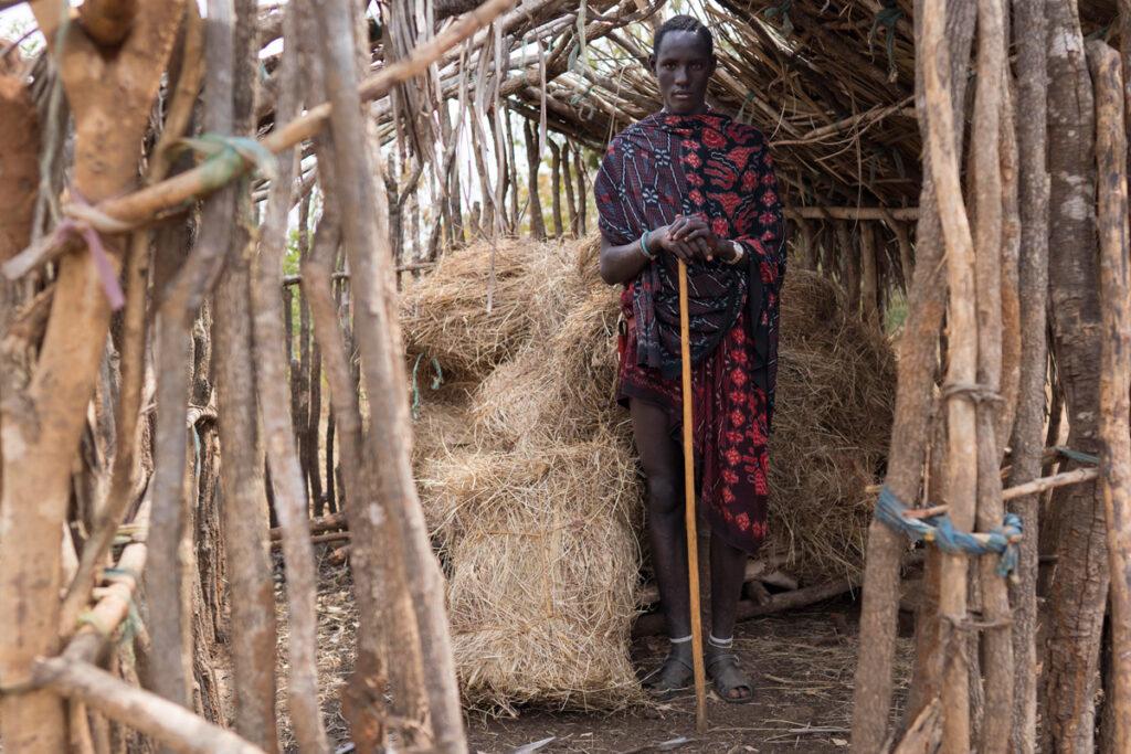 Junger Massai in Heuschuppen