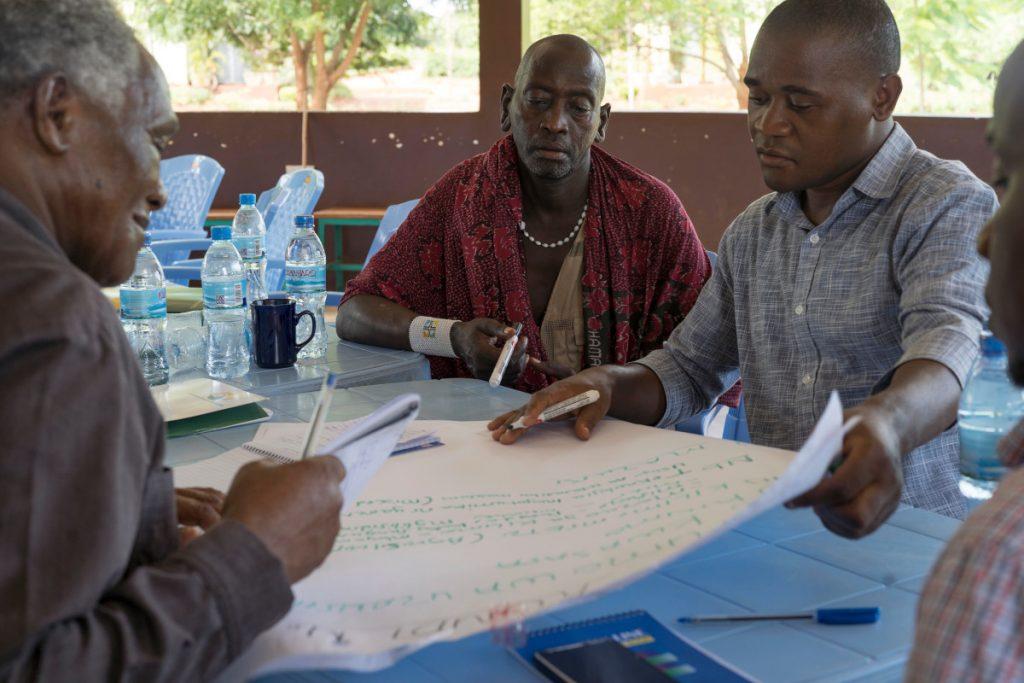 Drei Männer diskutieren und schreiben auf einem Plakat