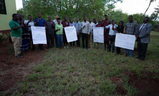 Teilnehmerinnen beim Workshop halten ihre Plakate hoch