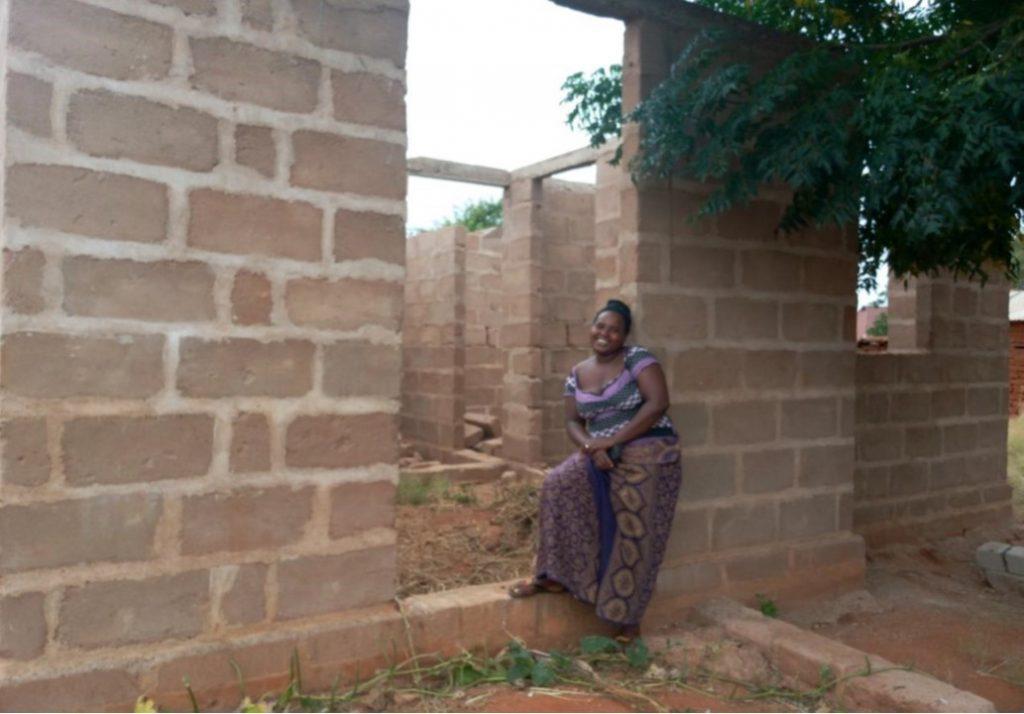 Frau vor ihrem Rohbau