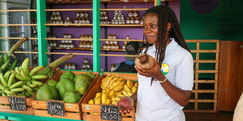 CEO Janet Maro hält Produkte des Bio-Shops in der Hand.